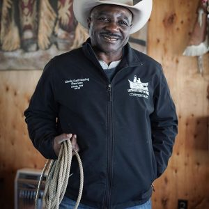 Maurice Wade in cowboy hat holding his rope